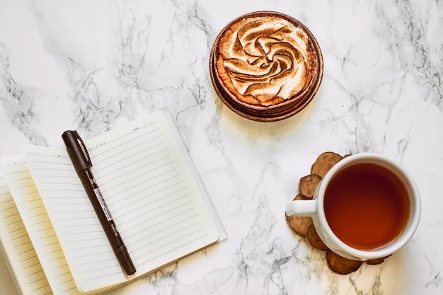 白い大理石の机の上での作業の上に健康的なケーキ。コピースペースのある上面図。