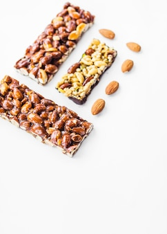 Healthy cereal and almonds bars against white background