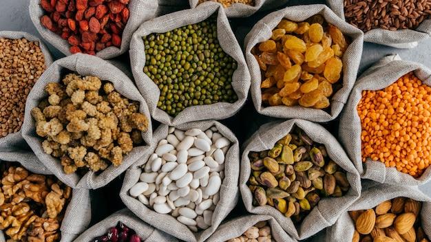 健康的なシリアルとドライフルーツ。乾燥マメ科植物の種子の小さな袋の平面図を閉じます。さまざまな種類の豆。天然の穀物。