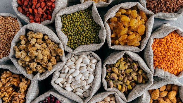 Healthy cereals and dried fruit. close up top view of small bags with dry legumes seeds. different types of beans. natural grains.