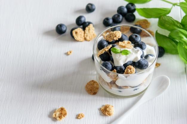 ヨーグルトとガラスのブルーベリーと健康的な穀物