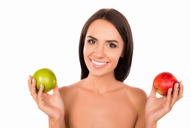 緑と赤のリンゴの間で選択する健康で陽気な若い女の子