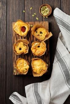 朝食にポレンタ、チェリートマト、カボチャの種を添えたヘルシーなチーズマフィン。セレクティブフォーカス。上面図。スペースをコピーします。