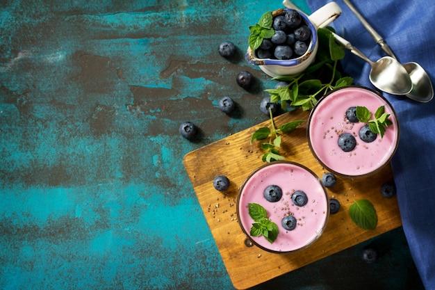 スレートテーブルにブルーベリーとグラスでヘルシーなチアシードプディングヘルシーな朝食トップビュー