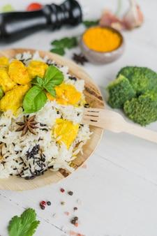 Здоровый куриный жареный рис; листья базилика в тарелке с деревянной вилкой и овощами