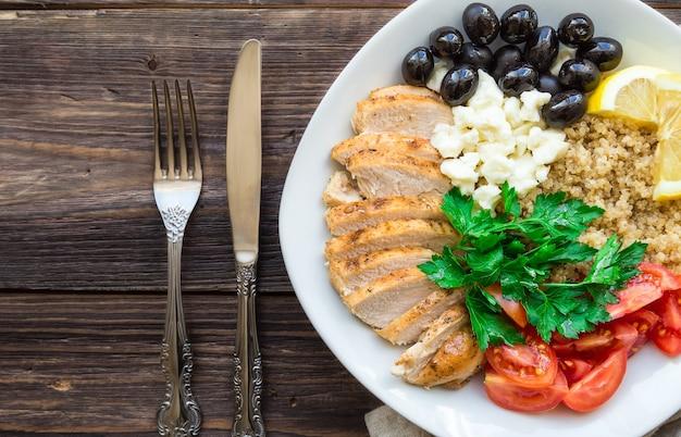 Здоровая куриная миска киноа с помидорами черри, фета, оливками и петрушкой на деревенском деревянном столе. вид сверху.