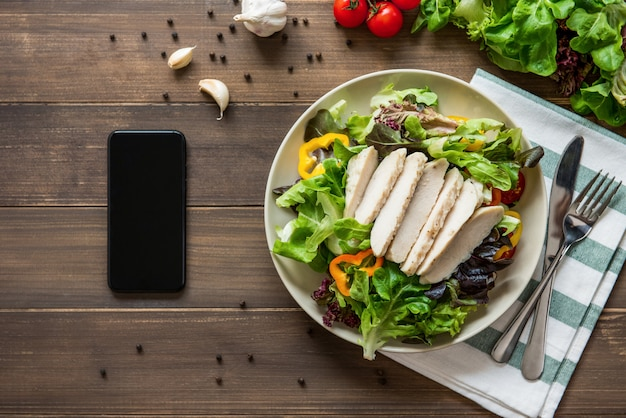 Healthy chicken salad next to smartphone on wood table background