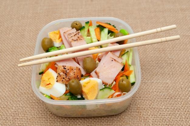 Полезный куриный салат с овощами в пластиковом контейнере с палочкой для еды