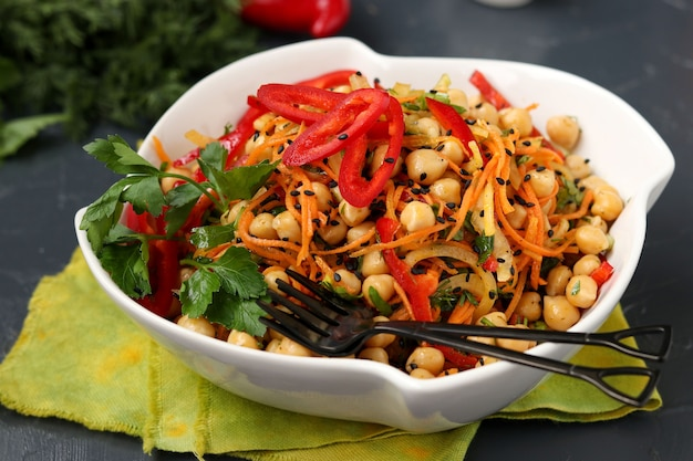 Healthy chickpea, korean carrot, sweet pepper and onion salad decorated with black sesame
