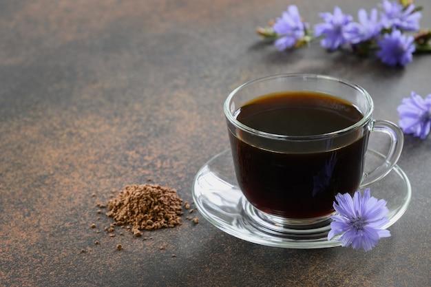 Здоровый напиток из цикория в стеклянной чашке, украшенной цветами цикория.