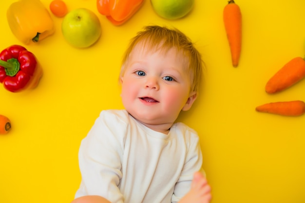 Здоровое детское питание, еда фон, вид сверху. улыбка ребенка 8 месяцев, в окружении различных свежих фруктов и овощей на желтом фоне. детское первое твердое вскармливание. детские с овощами