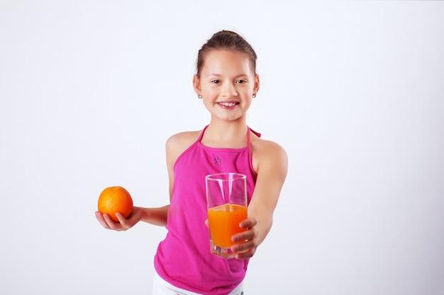 Здоровый ребенок с соком и апельсином. здоровая пища