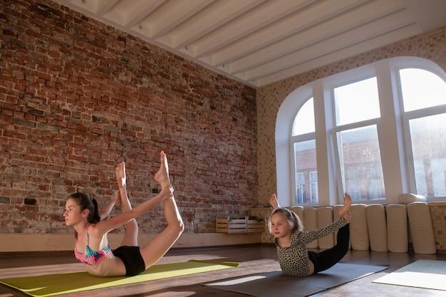 健康な子供のライフスタイル。体操の発達。 10代のスポーツ、子供のためのヨガ。スタジオでの女の子のためのストレッチ体操。ジムの背景、健康の概念