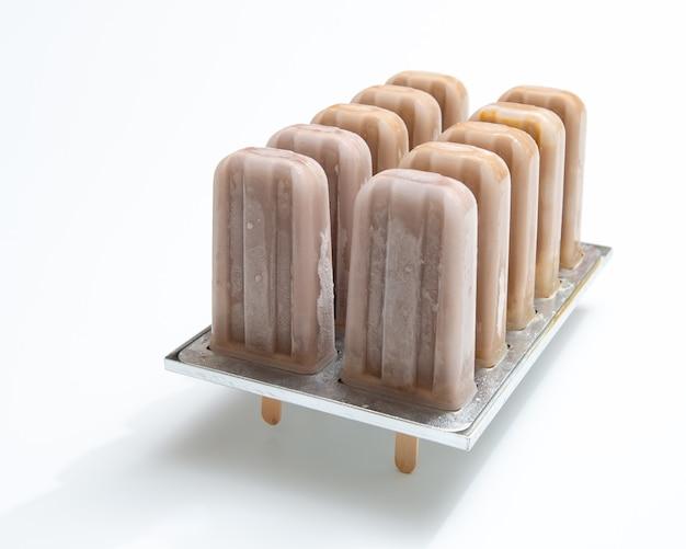 コピースペースと白い背景の形でスティック上の健康的なチョコレートアイスクリーム。美味しい冷たいデザート。