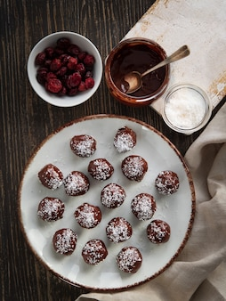 Healthy chocolate truffles with nuts, dates, dried cranberries and coconut flakes.