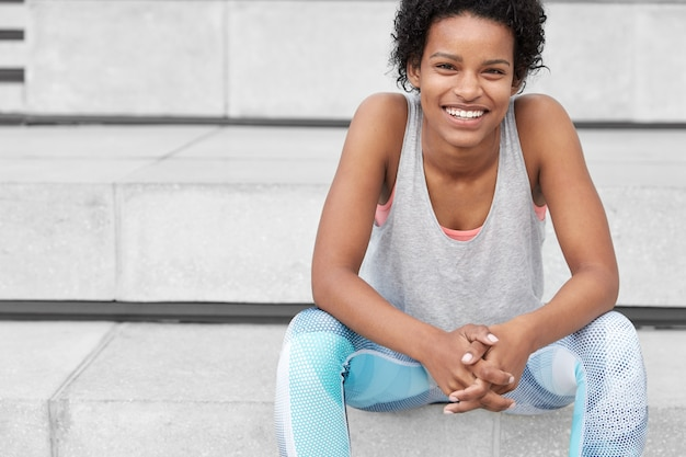 Healthy city lifestyle concept. shot of sporty mixed race teenage girl with dark skin, dressed in sportsclothes, has jogging break, sits at stairs, has toothy smile, has active training in open air