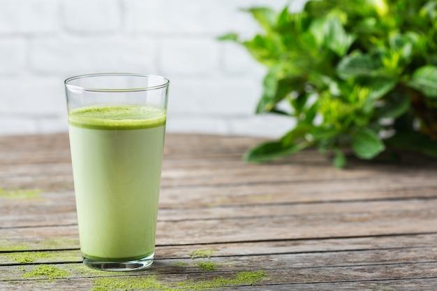 Концепция здорового чистого питания, утренний стол на завтрак. стакан модного латте зеленого чая матча на деревянном столе. уютная атмосфера кафе, копия космического фона