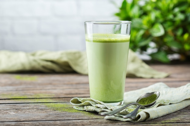 Концепция здорового чистого питания, утренний стол на завтрак. стакан модного латте зеленого чая матча на деревянном столе. уютная атмосфера кафе