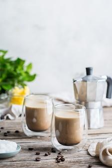 健康的なきれいな食事の概念、ケト、ケトン食療法、朝食の朝のテーブル。有機ココナッツオイル、ギーバター、コーヒー豆を使った防弾コーヒーの醸造。居心地の良いカフェの雰囲気