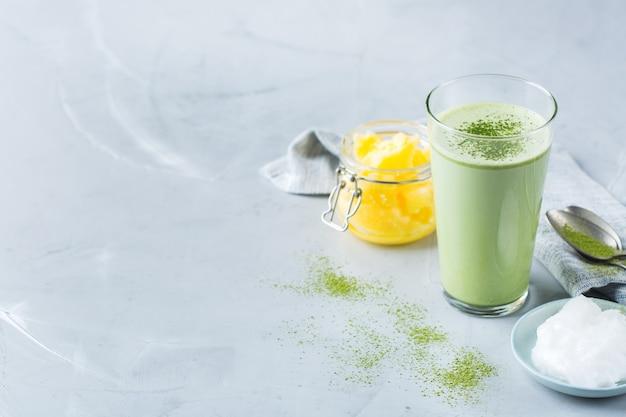 Концепция здорового чистого питания, кето, кетогенная диета, утренний стол для завтрака. пуленепробиваемый чай матча латте с органическим кокосовым маслом и топленым маслом. уютная атмосфера кафе, копия пространства