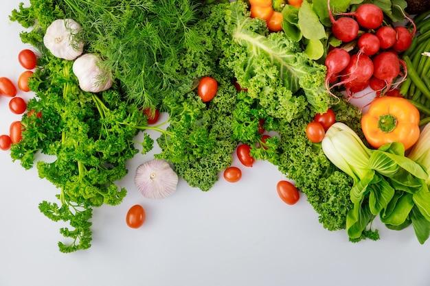 白い背景の上の健康的なカラフルな野菜。上面図。