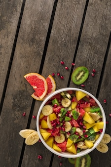 Healthy colourful fruit salad in bowl on wooden with copy space top view