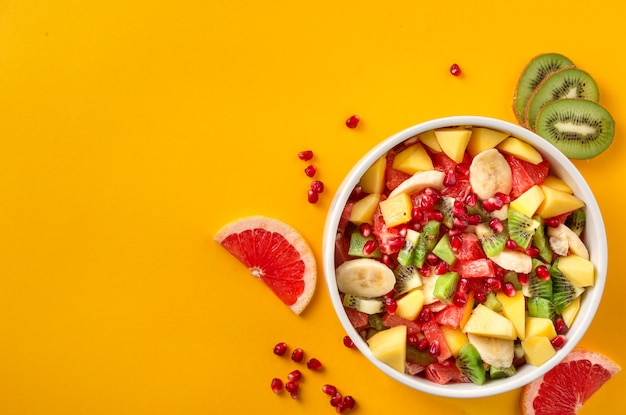 Healthy colourful fruit salad in bowl on yellow with copy space top view