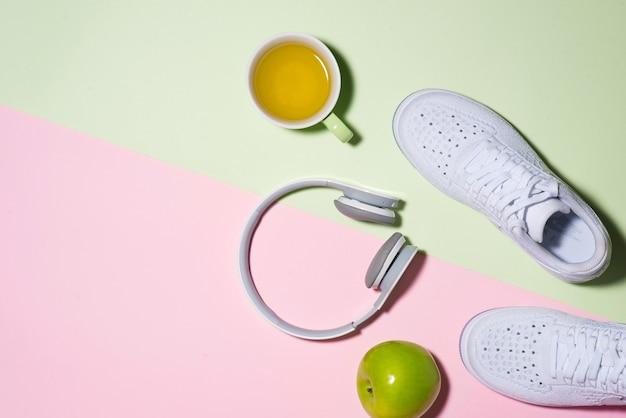 健康的なコンセプト。パステルカラーの背景にスニーカー、お茶、リンゴ、ヘッドフォン。