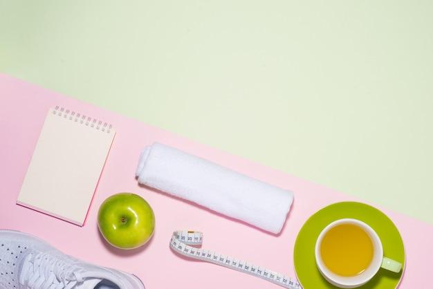 健康的なコンセプト。パステルカラーの背景にスニーカー、お茶、リンゴ、メジャーテープ。