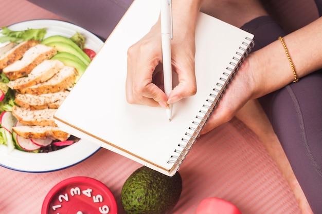 ランチボックスに栄養食品を入れた健康的なコンセプトと、日記帳で健康になるための時間を書く女性とのフィットネス機器