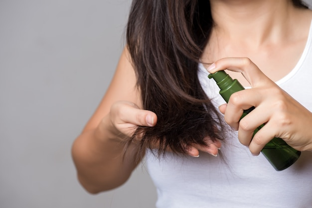 Healthy concept. woman hand holding damaged long hair with oil hair treatment