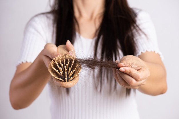 Healthy concept. woman show her brush with damaged long loss hair