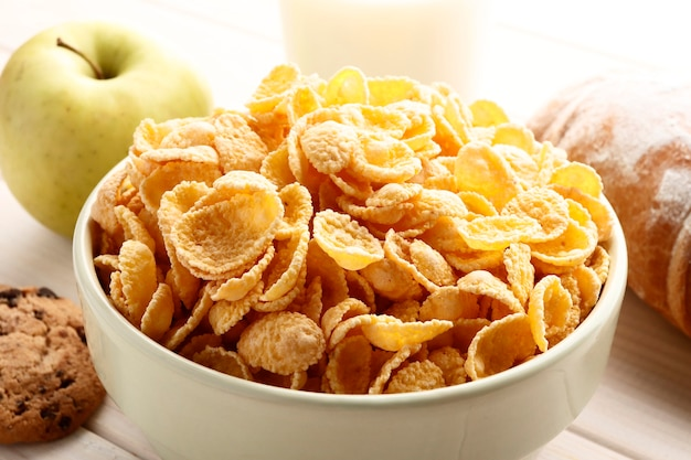 Healthy corn flakes with milk for breakfast with fruit.