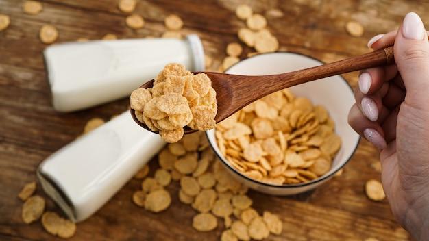 Здоровые кукурузные хлопья и молоко и деревянной ложкой на деревянном столе. стеклянные бутылки с молоком для здорового завтрака