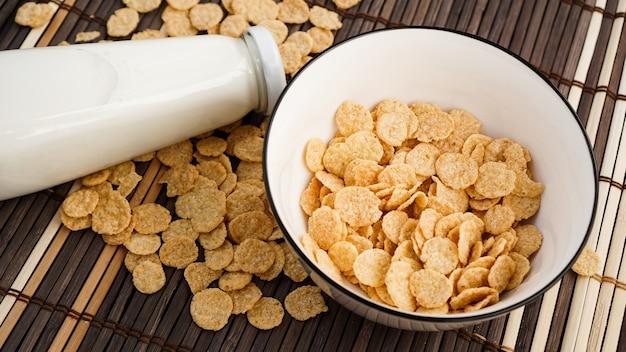 Здоровые кукурузные хлопья и молоко на бамбуковой салфетке. стеклянная бутылка с молоком для здорового завтрака