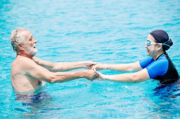 Здоровая пара старшая жена и муж любят играть вместе в бассейне