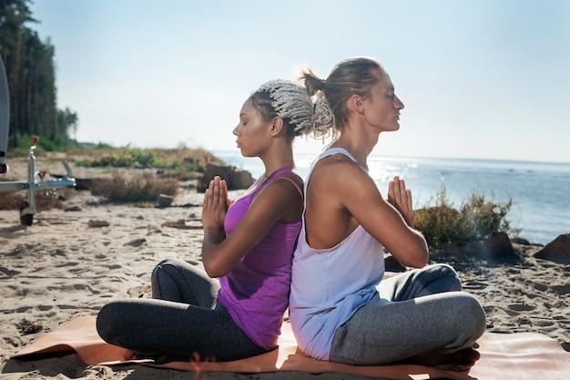 健康なカップル。川の近くの自然の中で一緒に瞑想しながらゆっくり呼吸する健康な愛情のあるカップル