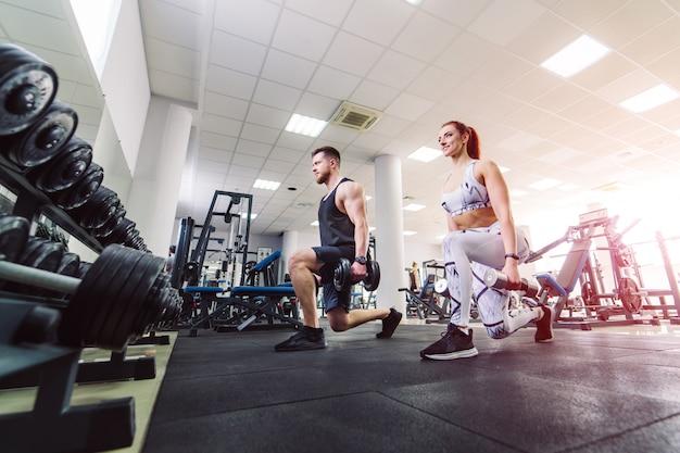 ジムでダンベルを持ち上げるスポーツ服で健康的なカップル。魅力的な女性とハンサムな男性は、スポーツクラブで特別なポーズで立っているダンベルでトレーニングを行います。