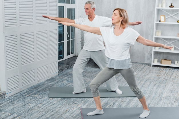 Healthy couple performing exercising on yoga mat at home