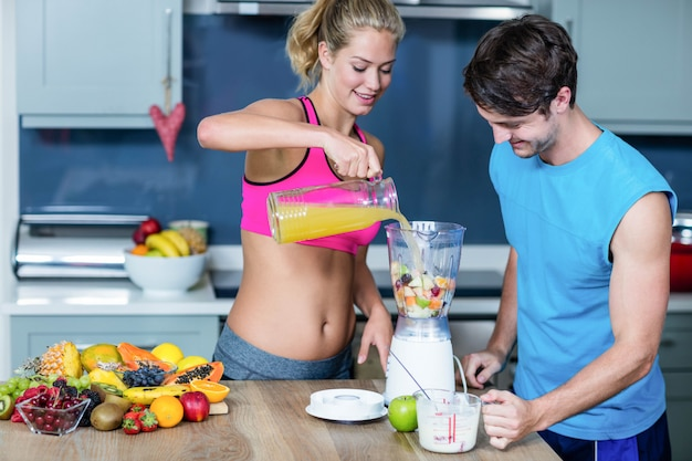 Healthy couple preparing a smoothie in the kitchen