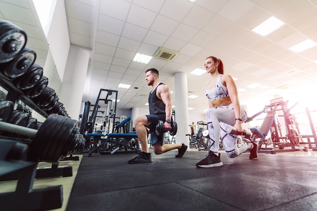 Healthy couple in sport clothes lifting dumbbells in the gym. attractive woman and handsome man doing workout with dumbbells standing in special pose in the sports club.