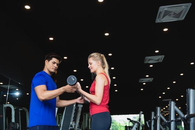 ジムでスポーツウェアでウェイトトレーニングを持ち上げる健康的なカップルトレーニング