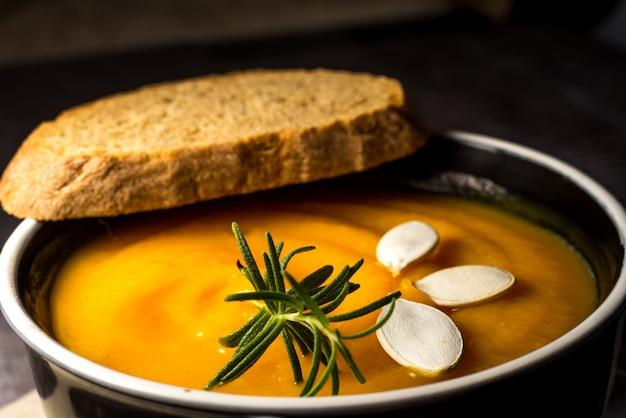 Здоровый крем из тыквенного супа на деревенский деревянный столик. осенний крем-суп из тыквы с розмариновыми травами и гренками. копировать пространство