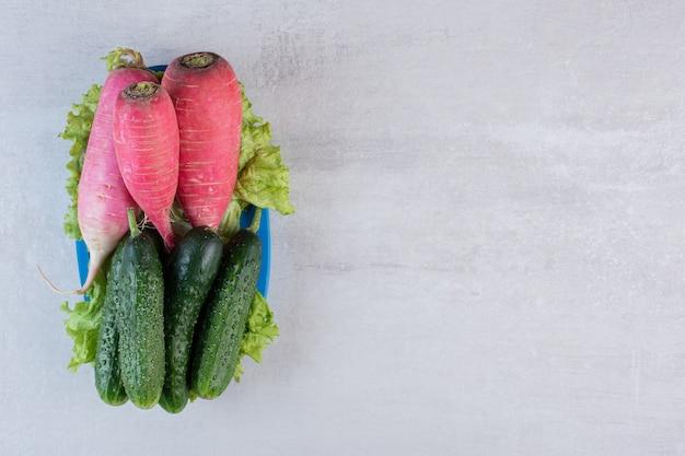 Здоровые огурцы и красный редис на синей тарелке. фото высокого качества