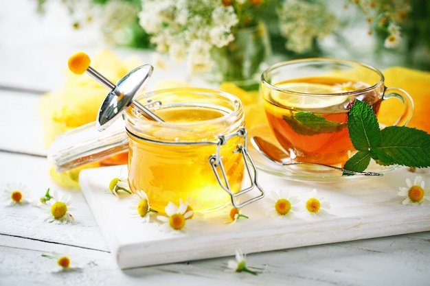 A healthy cup of tea, a jar of honey and flowers