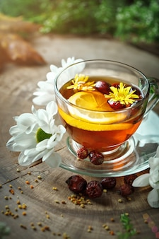 A healthy cup of tea with lemon and rose hips and flowers on a wooden table. selective focus.