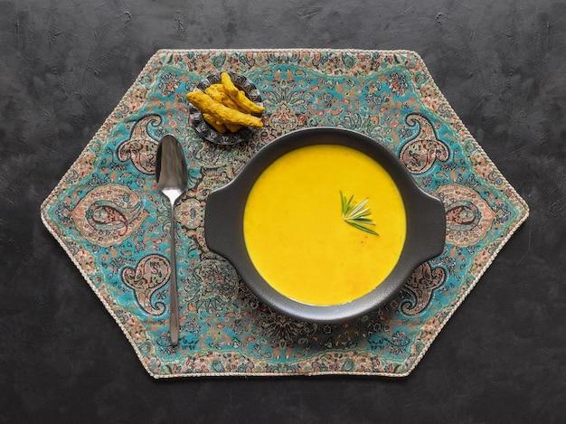 Healthy curcuma cream soup on black table
