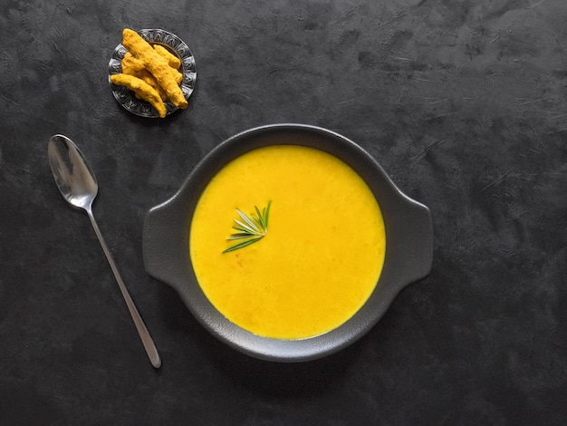 Healthy curcuma cream soup on black wall