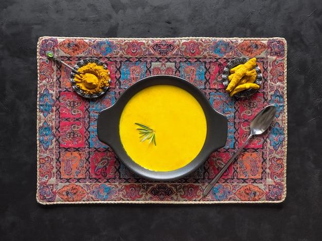 Healthy curcuma cream soup on black