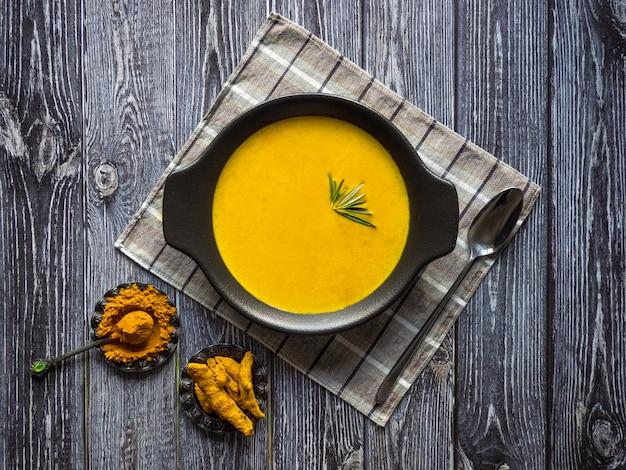 Здоровый куркума крем суп на черном деревянном